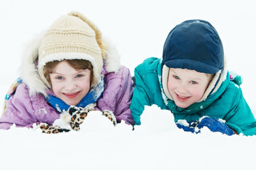 smiling happy children at winter snow outdoors