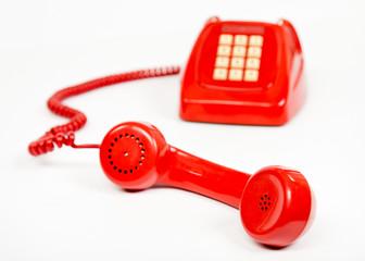 Teléfono rojo descolgado en fondo blanco.