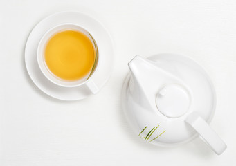 White tea pot and cup with yellow tea on white wooden board