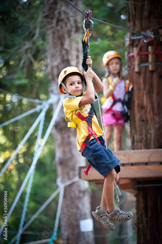 6 year old Kids climbing trees in Dolomites, Italy.