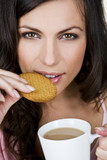 A young woman holding a cup of tea, eating a biscuit