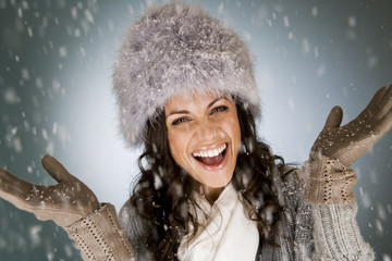 A young woman standing in the falling snow, smiling