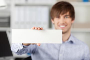 lächelnder mann im büro zeigt weißes schild