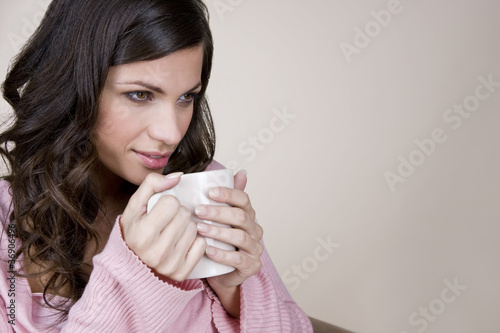 A young woman drinking a cup of hot chocolate