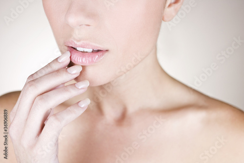 A young woman touching her lip