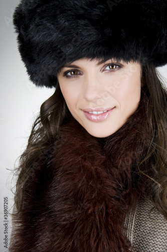 A young woman wearing a fur hat, smiling