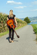 Guitarist walking down country road