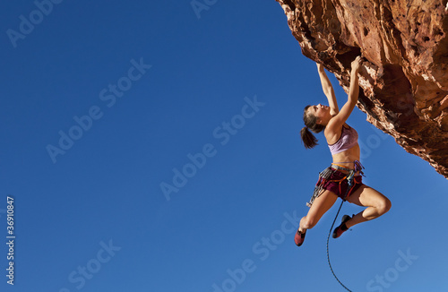 In de dag Persoonlijk Female climber clinging to a cliff.