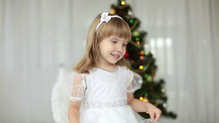 Happy angel swirls around Christmas tree