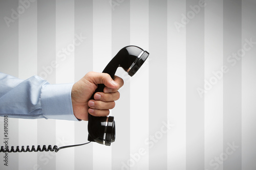 Human hand holding vintage telephone with copy space