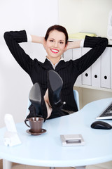 Businesswoman with legs laying on the desk