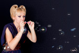 Woman with a hairdo blowing soap bubbles poster