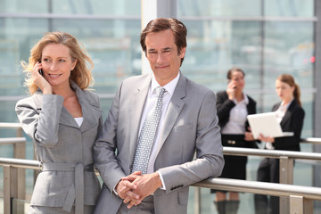 Male and female executives outside conference center
