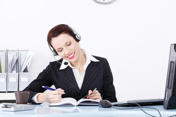 Writng businesswoman in headset.