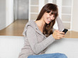 young woman smiles as she looks at her mobile phone