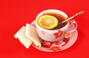 Cup of black tea with a lemon on a red cloth