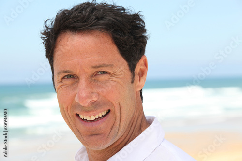 Man smiling at the seaside.