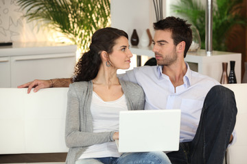 Couple relaxing on sofa with computer