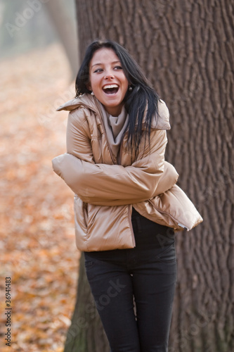 beautiful young woman laughing in autumn park