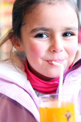 Young girl drinking a glass of orange juice