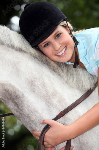 Blond girl riding horse