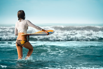 Sexy surf girl with surfboard on Bali beach
