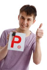 Teen boy holding driver P plates and car key