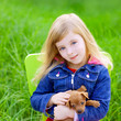 Blond kid girl with puppy pet dog in green grass