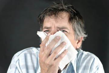 Man Sneezes Into Tissue Front