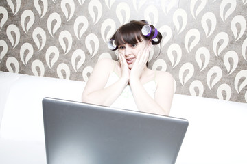 young adult beautiful girl with curlers on her head and laptop