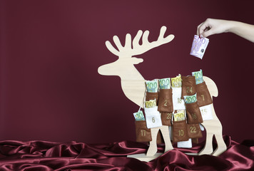 Euro bills are taken out of an advent calendar