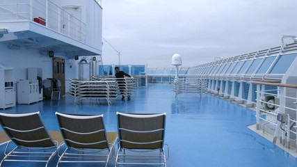Crew member stack sunbeds on deck of cruise liner