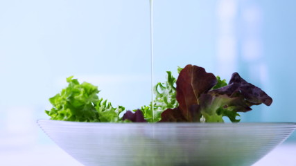 Pouring olive oil onto fresh salad