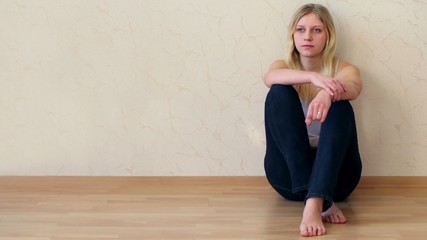 Young girl sits on floor with back pressed against wall