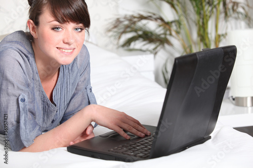 Cute woman using a laptop on her bed