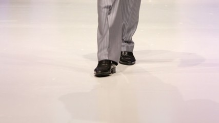Man walk in shoes by podium, only legs visible