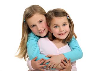 Two sisters hugging.