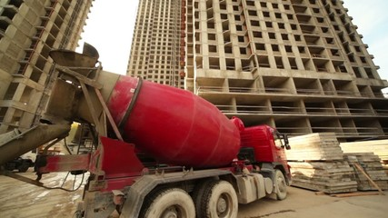 Concrete mixer stand near unfinished building