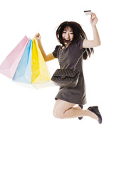 Jumping Chinese woman holding shopping bags and credit card.