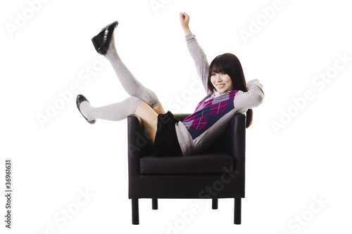 Excited Chinese student in a leather chair.