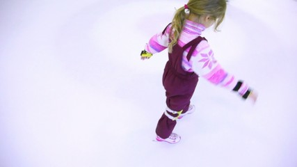 Little girl skates on ice towards the edge of rink