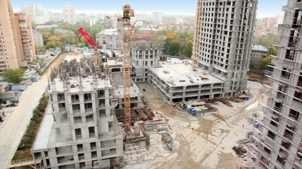 Construction site in foreground of cityscape of dormitory area