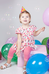 Little girl with balloons and soap bubbles in studio
