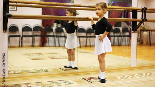 little girl crouches in ballet position