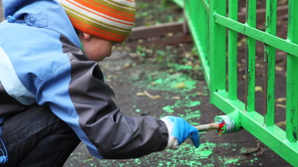boy with paintbrush in hand carefully dye fence by green