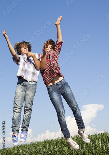 two boys jumping next to each other in the air