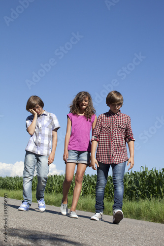 tired kids walking on a road