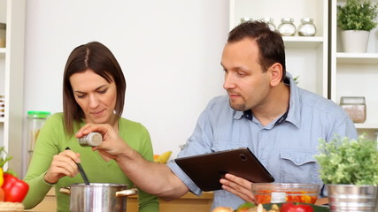 Couple using a tablet computer during cooking