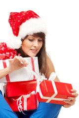 Girl in Santa hat  unwrapping her Xmas gifts