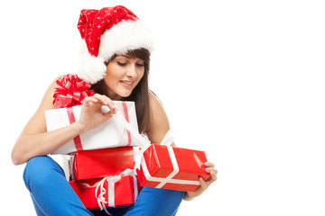 Girl sitting on the floor and unwrapping her Xmas gifts